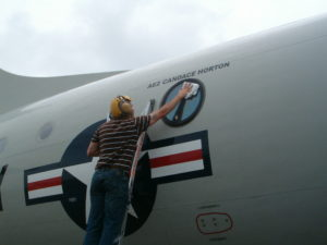 Member of the cast glance Navy P-3 crew polishing the viewing window on the aircraft